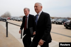 FILE - Secretary of Defense James Mattis greets John Bolton, left, as he arrives at the Pentagon in Washington, March 29, 2018.
