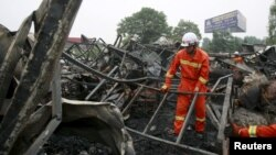 Firefighters clean up the debris after a fire at a rehabilitation center for the elderly in Sanlihe village of Pingdingshan, Henan province, China, May 26, 2015.