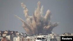 Asap dan pasir membubung ke udara menyusul serangan udara Israel di Gaza (25/8). (Reuters/Ahmed Zakot)