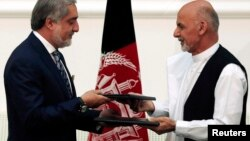 FILE - Afghan rival presidential candidates Abdullah Abdullah (L) and Ashraf Ghani exchange signed agreements for the country's unity government in Kabul, Sept. 21, 2014.