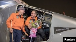 "Pilot Andre Boschberg (R) chats with pilot Bertrand Piccard after Boschberg landed ""Solar Impulse 2"" in Muscat, Oman, March 9, 2015."
