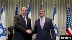 20일 이스라엘 텔아비브에서 애슈턴 카터 미 국방장관(오른쪽)과 모셰 얄런 이스라엘 국방장관이 만나 악수하고 있다.
