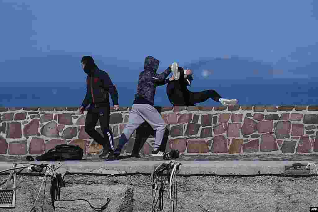 A journalist (R) is attacked by residents who are trying to prevent migrants from disembarking on the Greek island of Lesbos.