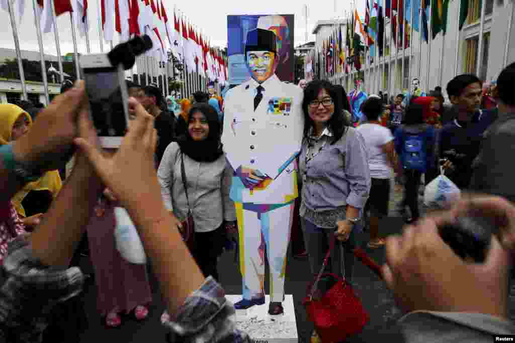 People pose for pictures with a statue of Indonesia's first president Soekarno in Bandung, Indonesia, April 24, 2015.