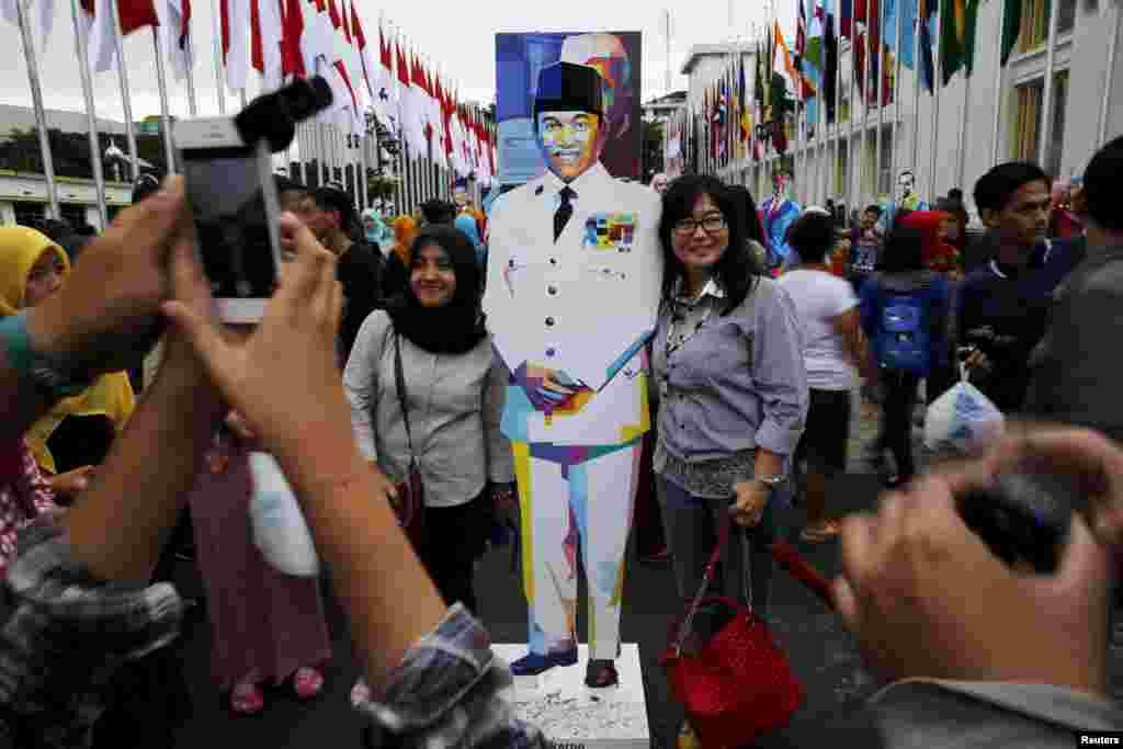 Watu wapiga picha pamoja na sanamu ya rais wa kwanza wa Indonesia, Bw.Soekarno mjini Bandung, Indonesia, mtu aliyesukuma kuanzishwa kwa uhusiano huo wa kihistoria. April 24, 2015.
