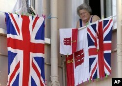 FILE - A woman resident of Gibraltar looks out of a window behind flags of England and Gibraltar, Aug. 4, 2004.