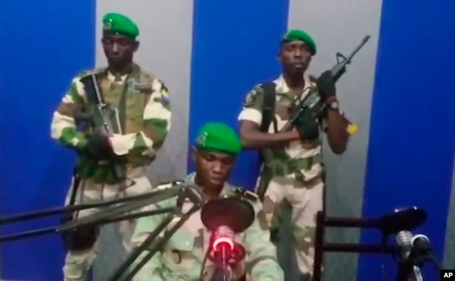 In this image from TV, a soldier who identified himself as Lt. Obiang Ondo Kelly, commander of the Republican Guard, reads a statement on state television broadcast from Libreville, saying the military has seized control of the government, Jan. 7, 2019.