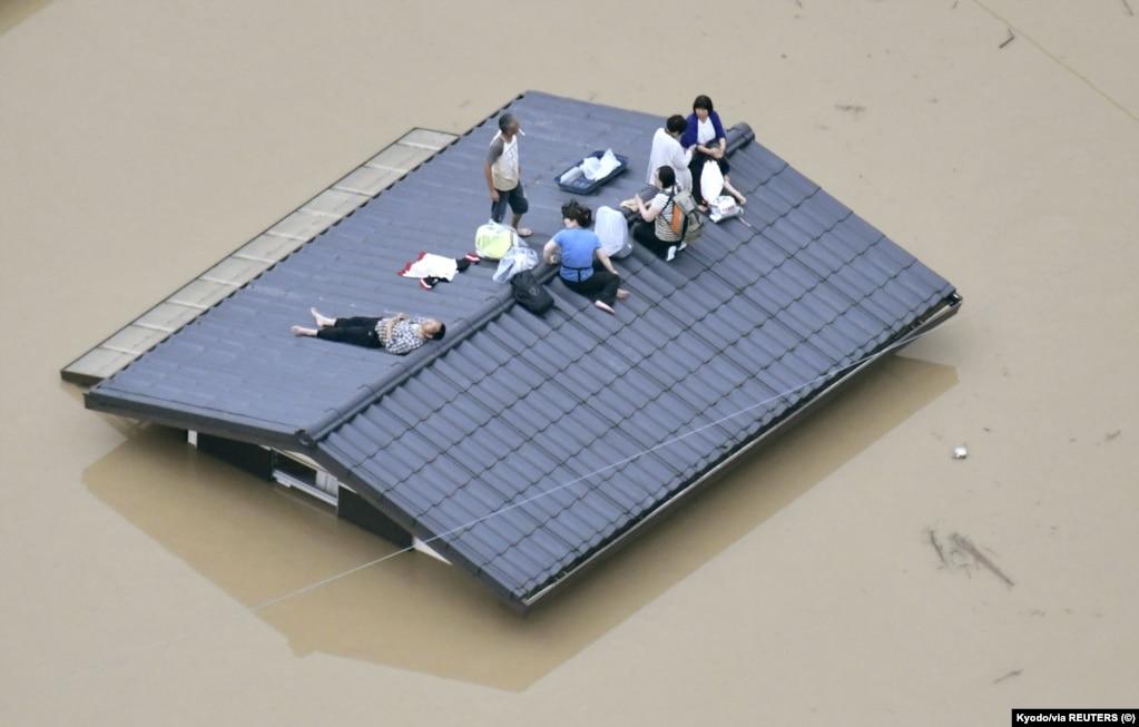 Yaponiyanın cənubunda Kuraşikidə evlərini sel basmış insanlar yardım gözləyir. .
