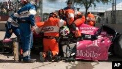 Esfuerzo por rescatar a Darío Franchitti, de su auto luego de chocar contra una barrera en el Gran Premio Indy de Houston.