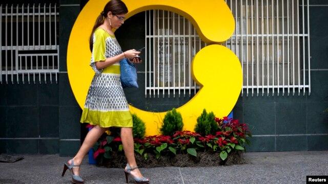Una empleada de Globovisión camina frente a al edificio principal de la televisora, censurada por el gobierno por octava vez en ocho años.