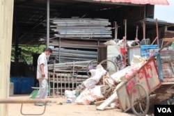 Mao Tran surveys piles of scraps stored at a rented warehouse in Phnom Penh, Cambodia, April 22, 2020. (Phorn Bopha/VOA Khmer)