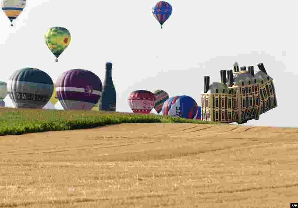 "Hot-air balloons fly near Chambley-Bussieres, eastern France, on the first day of the international air-balloon meeting ""Lorraine Mondial Air Ballons."""