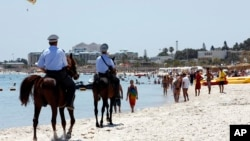 FILE - Mounted police officers patrol on the beach of Sousse, Tunisia, June 28, 2015.