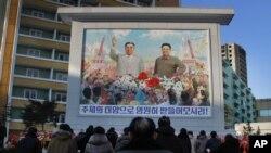朝鲜人聚集在金日成像和金正日像前,纪念金正日去世三周年(2014年12月17日)