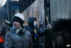 Những người biểu tình hôm thứ Sáu đã chiếm một tòa nhà chính phủ ở thủ đô Ukraina trong khi tiếp tục duy trì việc chiếm đóng văn phòng của một số thống đốc ở phía tây nước này, tiếp tục gia tăng áp lực lên chính phủ. (AP/Sergei Grits)