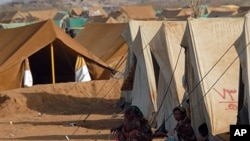 FILE - Displaced Yemeni women from the Saada province sit outside a tent at the Mazraq Internally Displaced People's (IDP) camp in northern Yemen.