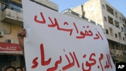 "Syrians protest in the city of Banias holding up a sign that reads in Arabic, ""Stop the innocent blood bath"" on April 26, 2011"
