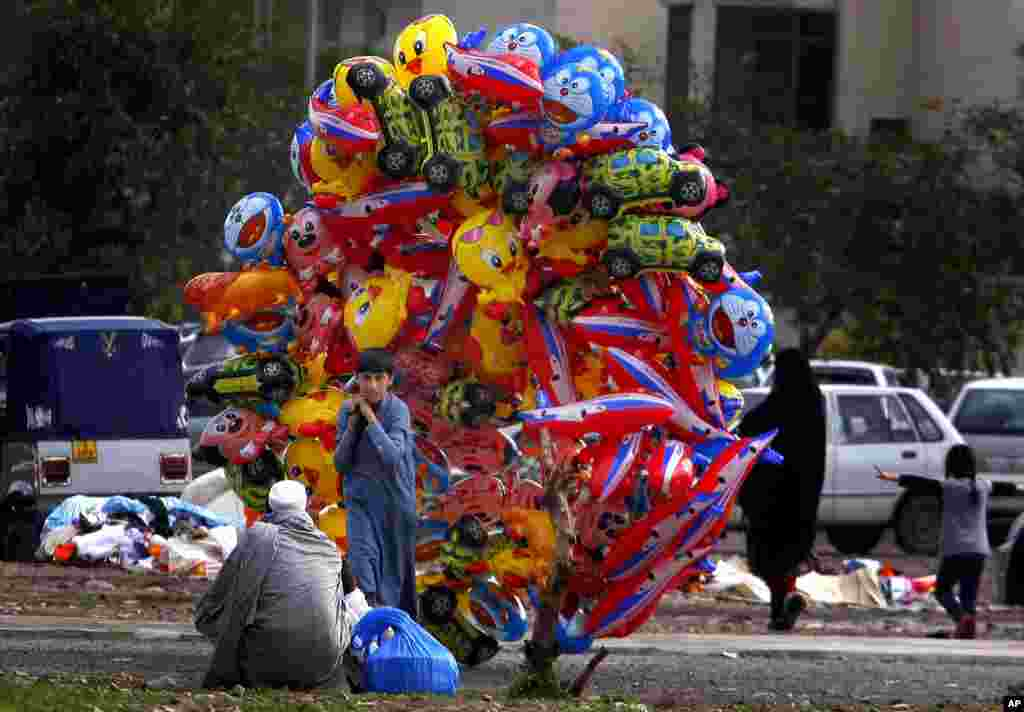 A boy sells balloons on a street in Peshawar, Pakistan.