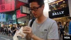 參觀街頭六四小型展覽的香港大專學生關同學在現場縫製「小民女包包」(美國之音湯惠芸拍攝)
