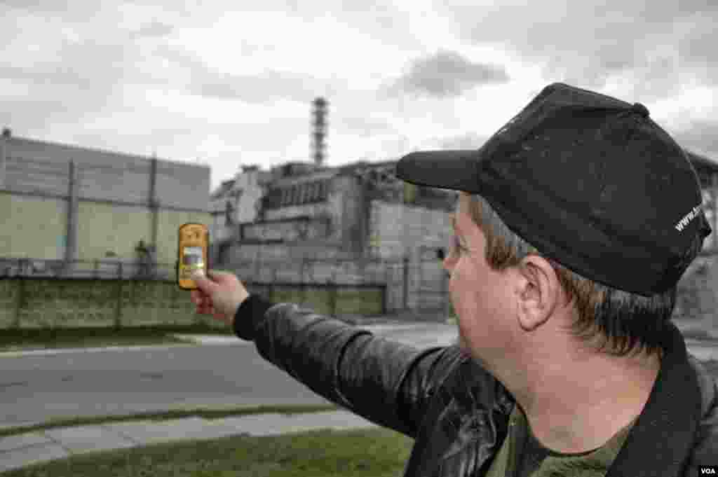 Driver Igor Bordnarch, a frequent visitor to the Chernobyl reactor site, checks radiation readings just 240 meters from the destroyed reactor. (Steve Herman/VOA)