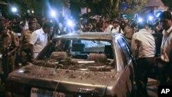 ຕຳຫຼວດນອກເຄື່ອງແບບອິນເດຍ ພວມຫ້ອມລ້ອມລົດຄັນນຶ່ງ ທີ່ໄດ້ຮັບຄວາມເສຍຫາຍ ຍ້ອນເຫດລະເບີດ ທີ່ຄຸ້ມ Dadar ຂອງນະຄອນມູມໄບ (13 ກໍລະກົດ 2011)