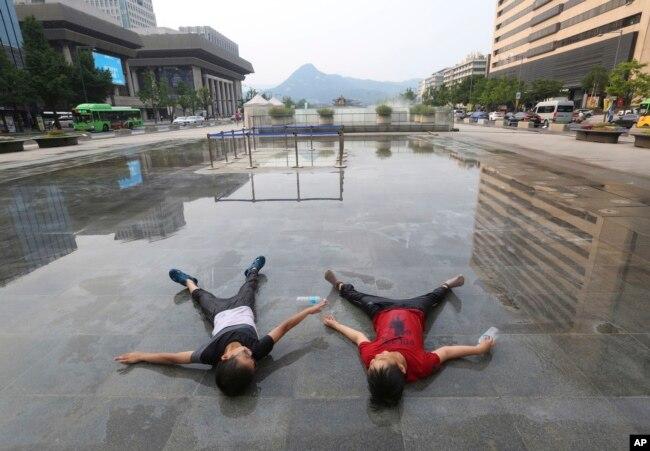 Хлопчики чекають, поки ввімкнеться фонтан у Сеулі, Південна Корея, де температура досягла вище 37 градусів за Цельсієм. 24 липня 2018 року.
