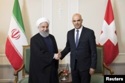 Swiss Federal President Alain Berset and Iranian President Hassan Rouhani shake hands at the beginning of a meeting during Rouhani's official visit to Switzerland in Bern, Switzerland, July 2, 2018.
