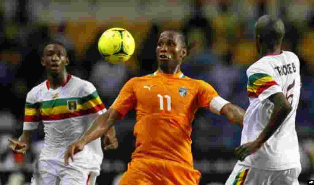 Ivory Coast's Didier Drogba (C) controls the ball between two Mali players during their African Nations Cup semi-final soccer match at the Stade De L'Amitie Stadium in Gabon's capital Libreville February 8, 2012.