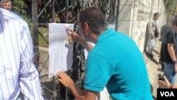 Un hombre revisa el número de su mesa electoral para ingresar a sufragar en Venezuela. [Foto: Alvaro Algarra, VOA].