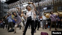 "FILE - Elderly and middle-age people exercise with wooden dumbbells during a health promotion event to mark Japan's ""Respect for the Aged Day"" at a temple in Tokyo's Sugamo district, an area popular among the Japanese elderly, Sept. 21, 2015."