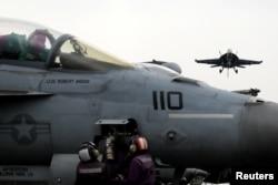 ທະຫານເຮືອ ອາເມຣິກັນຄົນນຶ່ງ ພວມກວດເບິ່ງ ເຮືອບິນລົບ F-18 ແລະເຮືອບິນລົບ F-18 ກຽມລົງຈອດ ທີ່ເຮືອກຳປັ່ນ ບັນທຸກເຮືອບິນ ແຮຣີ ທຣູແມນ ໃນທະເລເມດິແຕເຣນຽນ. (ວັນທີ 4 ພຶດສະພາ 2018)