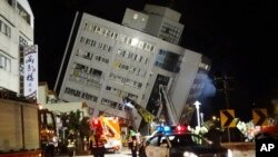 Rescuers are seen entering a building that collapsed onto its side from an early morning 6.4 magnitude earthquake in Hualien County, eastern Taiwan, Feb. 7 2018. Rescue workers are searching for any survivors trapped inside the building.
