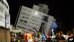 Rescuers are seen entering a building that collapsed onto its side from an early morning 6.4 magnitude earthquake in Hualien County, eastern Taiwan, Wednesday, Feb. 7 2018. Rescue workers are searching for any survivors trapped inside the building.