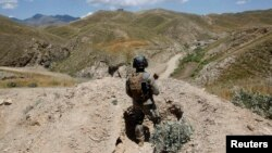 FILE - An Afghan border policeman is seen patrolling a section of the frontier between Afghanistan and Pakistan.