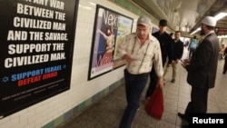 "FILE - Cyrus McGoldrick, a member of the Council on American-Islamic Relations, talks to commuters as they walk by an advertisement that reads ""Support Israel/Defeat Jihad"" in the Times Square subway station in New York, Sept. 24, 2012."