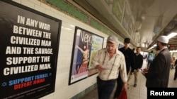Un passager du métro passant devant l'une des affiches dénonçant les musulmans