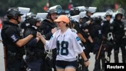 یکی از تماشاچیان بازی فوتبال آمریکایی در شارلوت پس از ترک استادیوم با ماموران پلیس ضد شورش صحبت می کند