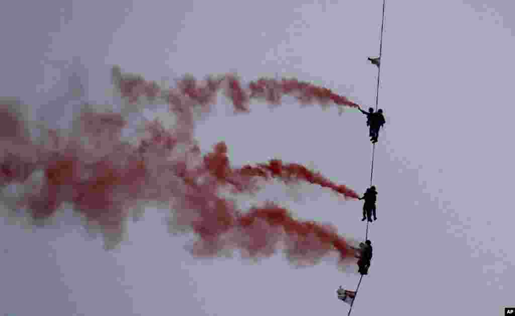 Indian Navy personnel display their skills during a rehearsal for Naval Day celebrations at the Arabian Sea in Mumbai.