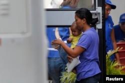 2014年7月14日洪都拉斯北部圣佩德罗苏拉国际机场,一名妇女和她的儿子进入一辆载有从美国遣返回国者的汽车前往车站。