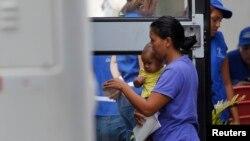 Một phụ nữ và con trai của cô bước lên chiếc xe buýt chở những người bị trục xuất từ Mỹ đến trạm xe, 14/7/2014.