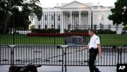 Anggota Dinas Rahasia berjaga-jaga di depan Gedung Putih.