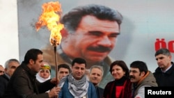 Selahattin Demirtas (front C), co-chairman of the pro-Kurdish Peace and Democracy Party (BDP), lights a traditional Newroz fire during a rally to celebrate the spring festival of Newroz - with a picture of imprisoned PKK leader Abdullah Ocalan seen in the