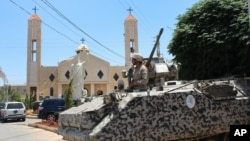 A Lebanese army soldier from the special forces unit stands on a APC during a patrol in front a church in Qaa, a predominantly Lebanese Christian village near the Syrian border were suicide bombers blow themselves among civilians on Monday, eastern Lebano
