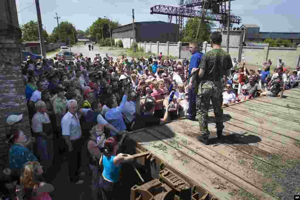 Vyacheslav Ponomarev, (foreground, in blue), the self-proclaimed mayor of Slovyansk, speaks to local citizens whose homes were demolished by shellfire, in Slovyansk, eastern Ukraine, May 20, 2014.