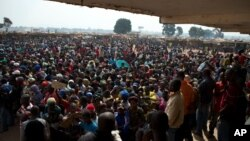 People wait to receive food and supplies from an aid distribution point set up inside a makeshift camp at Mpoko Airport in Bangui, Jan. 7, 2014.
