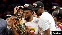 Kawhi Leonard, à gauche, tient le trophée de champion NBA, USA, le 13 juin 2019.