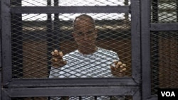 Al-Jazeera English correspondent Peter Greste appears in a defendant's cage in a courtroom in the Police Institute Court House in Tora, along with several other defendants during their trial on terror charges, in Cairo, Egypt, April 22, 2014. (Hamada Elra