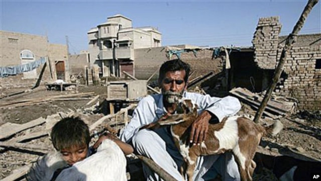 Flood survivor Kalo Jamali sits with his goats and a child in remains of his house destroyed by floods in the village Khairpur Nathan Shah, Pakistan, which is still surrounded by floodwaters, Nov 2, 2010