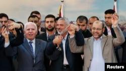 Pemimpin Fatah Azzam Al-Ahmed (kiri), pemimpin Hamas Ismail Haniyeh (tengah) dan Moussa Abu Marzouq bergandeng tangan saat rekonsiliasi di Gaza bulan April lalu (foto: dok).