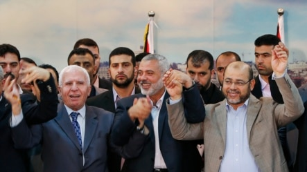Senior Fatah official Azzam Al-Ahmed (L), head of the Hamas government Ismail Haniyeh (C) and senior Hamas leader Moussa Abu Marzouq hold their hands after announcing a reconciliation agreement in Gaza City, April 23, 2014.